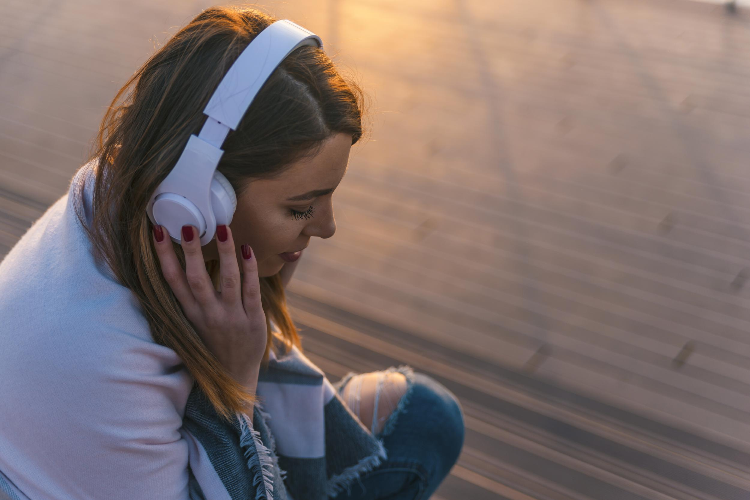 Portrait of young woman with headphones sitting on pier and listening music on sunset.jpeg