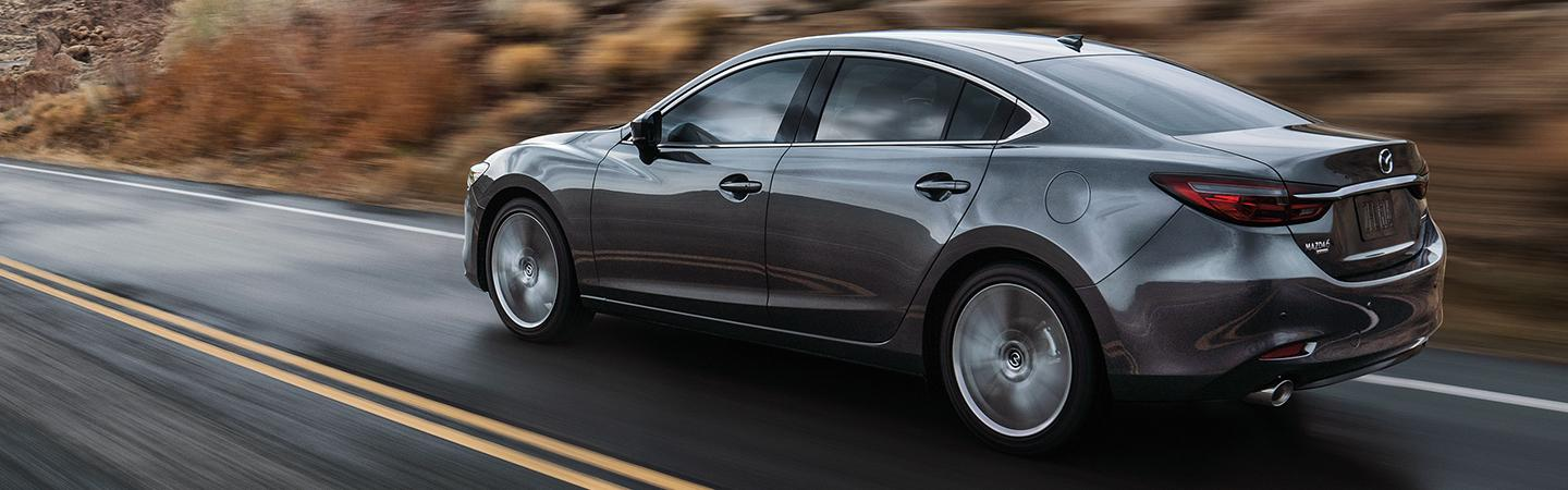 Side rear view of the 2020 Mazda6 driving straight