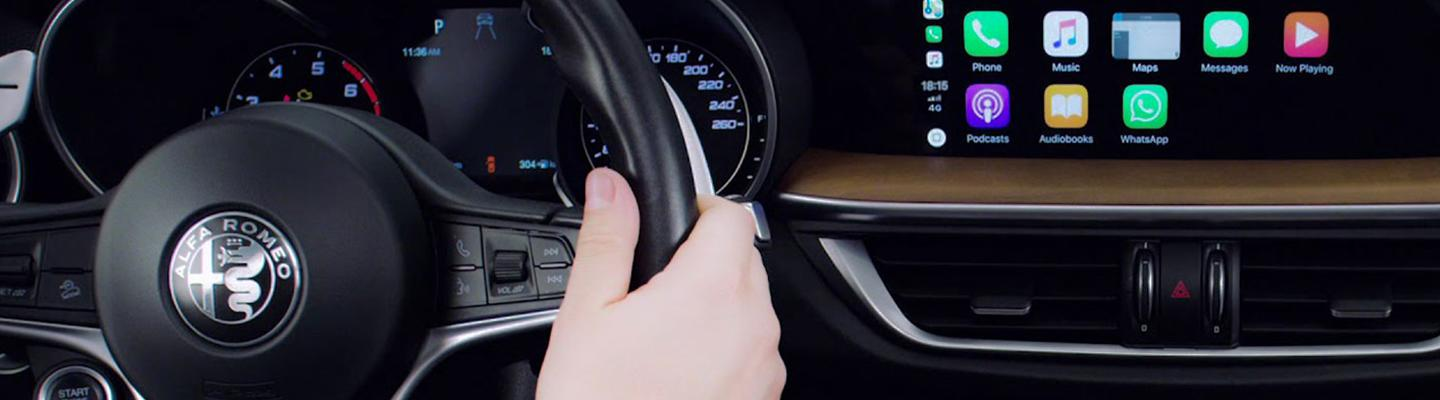 Close-up of an Alfa Romeo steering wheel and infotainment system showing apps.