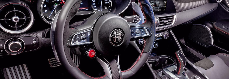 Close-up of a 2021 Alfa Romeo Giulia steering wheel and dash.