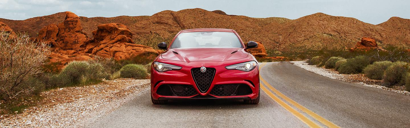 Front view of a red 2021 Alfa Romeo Giulia parked in the desert.