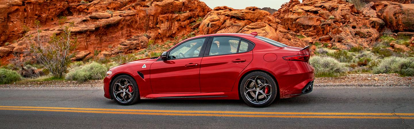 Side view of a red 2021 Alfa Romeo Giulia parked in the desert.
