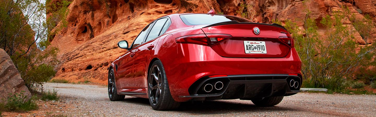 Rear view of a red 2021 Alfa Romeo Giulia parked in the desert.