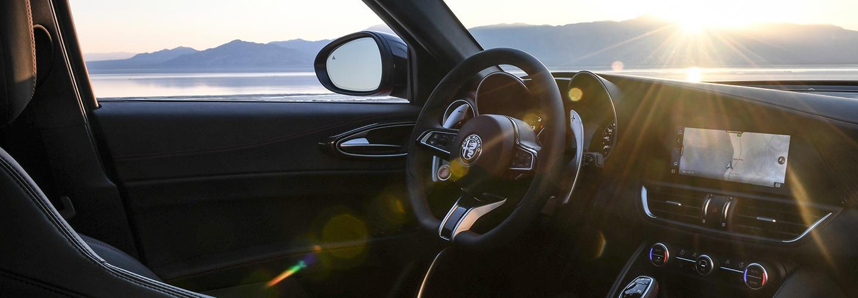 Passenger-side view of the 2021 Alfa Romeo Giulia Quadrifoglio steering wheel and infotainment system.
