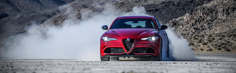 Front view of a red 2021 Alfa Romeo Giulia Quadrifoglio kicking up dust.