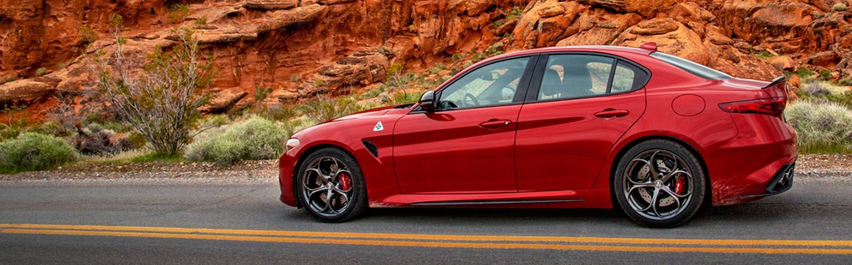 Side view of a red 2021 Alfa Romeo Giulia Quadrifoglio parked in the desert.