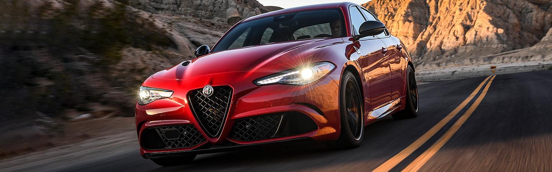 Close-up of the front of a red 2021 Alfa Romeo Giulia Quadrifoglio driving down the road.