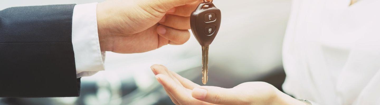 Salesman handing new keys to a woman