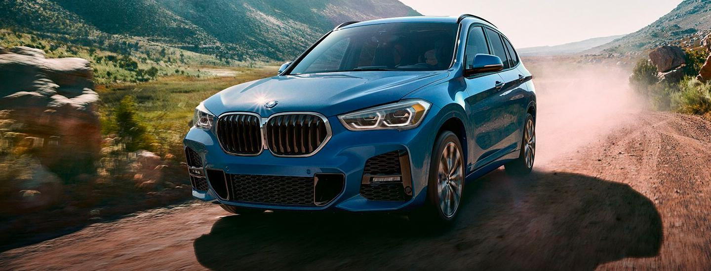 Blue 2020 BMW X1 driving on a dirt road