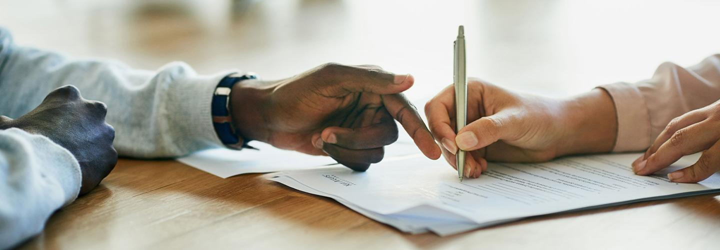 A customer and financial advisor signing lease paperwork