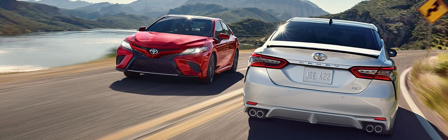 Two 2020 Toyota Camry vehicles driving on the road