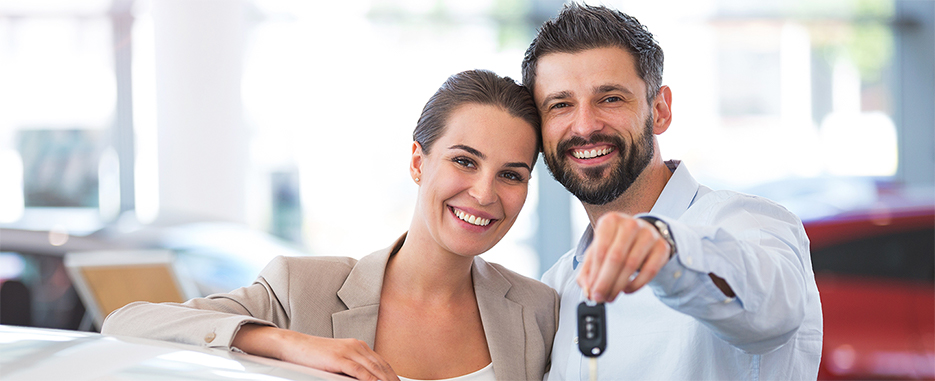 HAPPY COUPLE HOLDING UP CAR KEYS