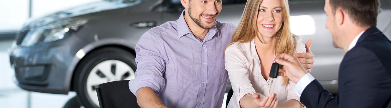 happy couple taking keys from salesman