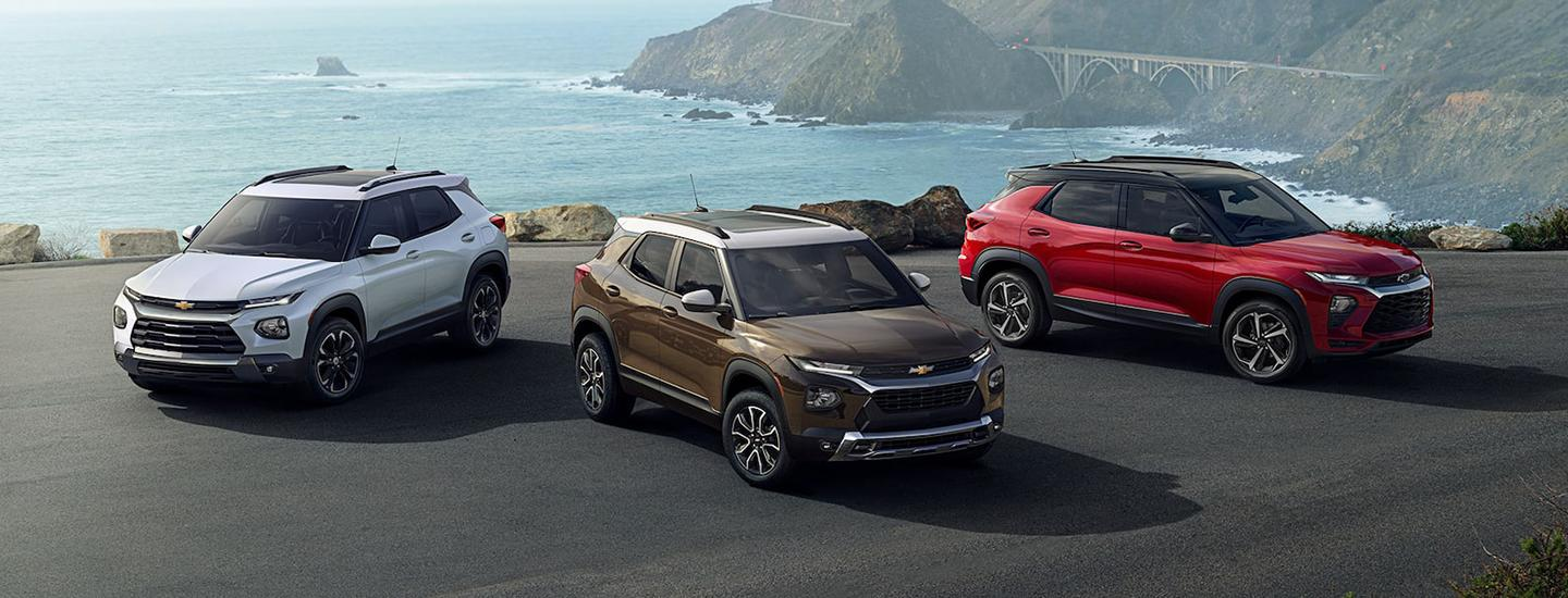 Three Chevy Trailblazers parked on an oceanside mountain road