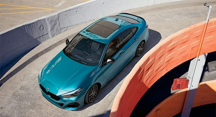 Blue 2020 BMW 2 Series Gran Coupe driving down a parking garage