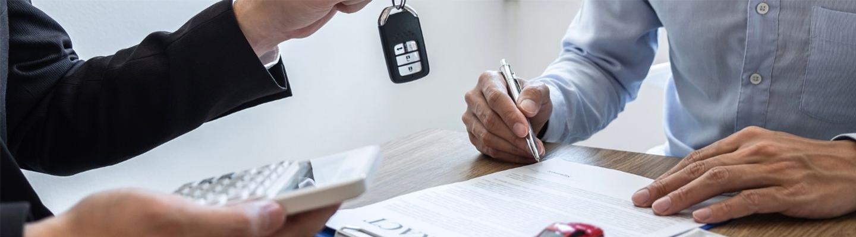 A closeup view of a dealership employee handing off car keys