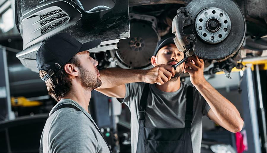Two service tech working on the brakes of a Kia