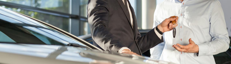 Closeup view of a dealership employee handing car keys to a customer