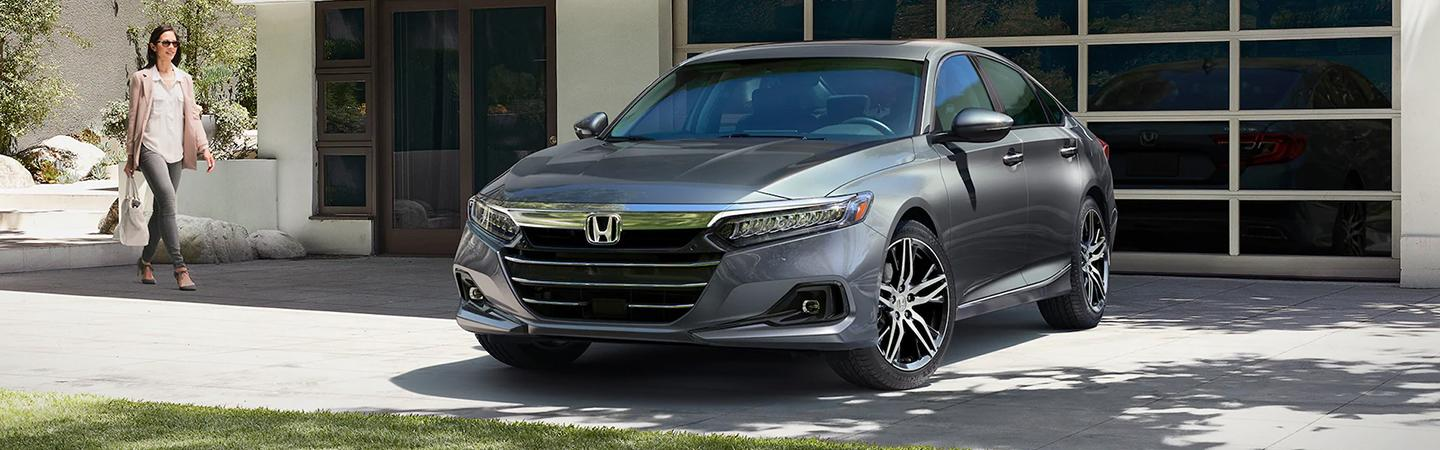 A driver walking to their dark gray Honda Accord parked in a driveway