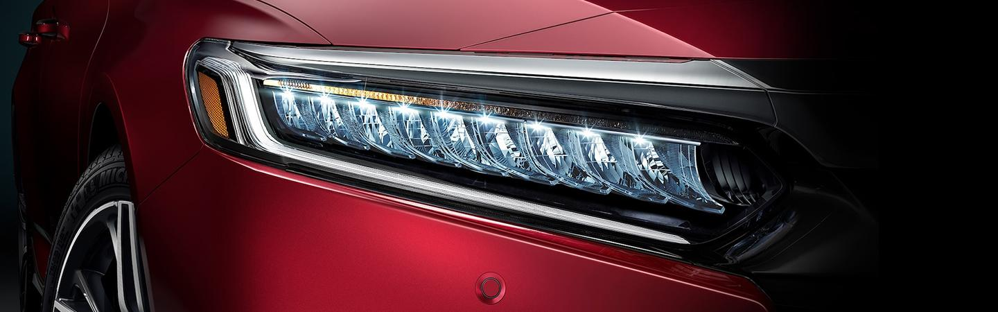 Close up view of a red Honda Accord's headlight