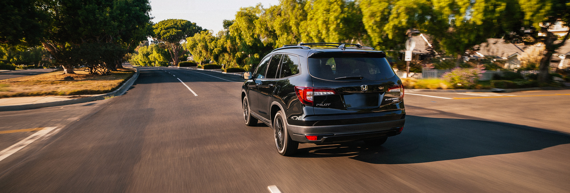 Rear view of a black Honda Pilot in motion
