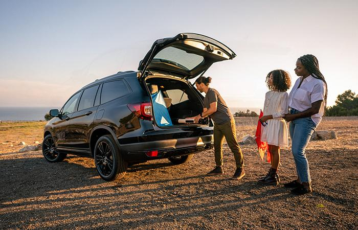 Friends unloading the trunk of their black Honda Pilot