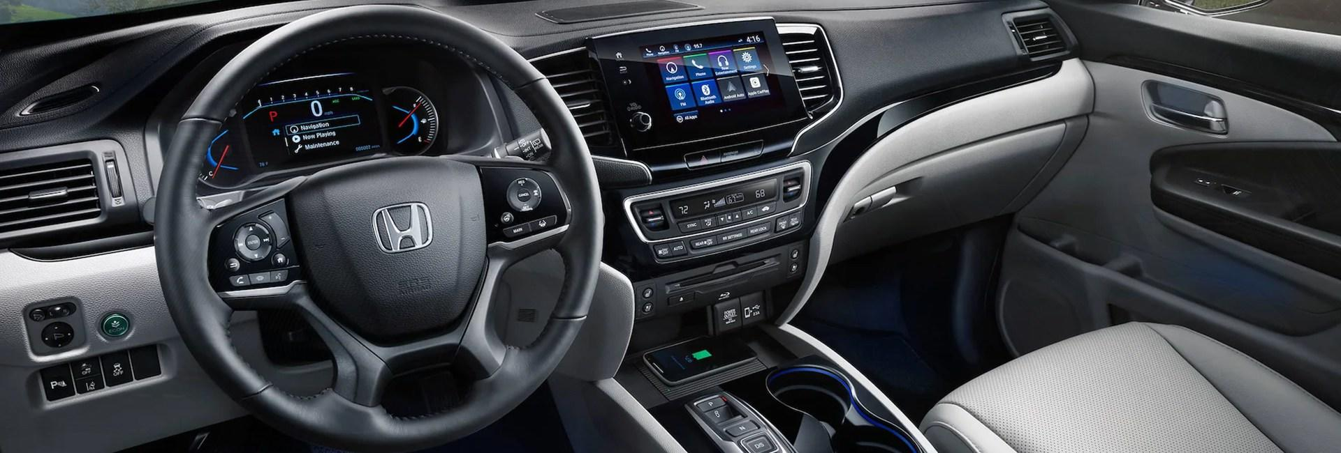 Close up view of a Honda Pilot's steering wheel and dashboard