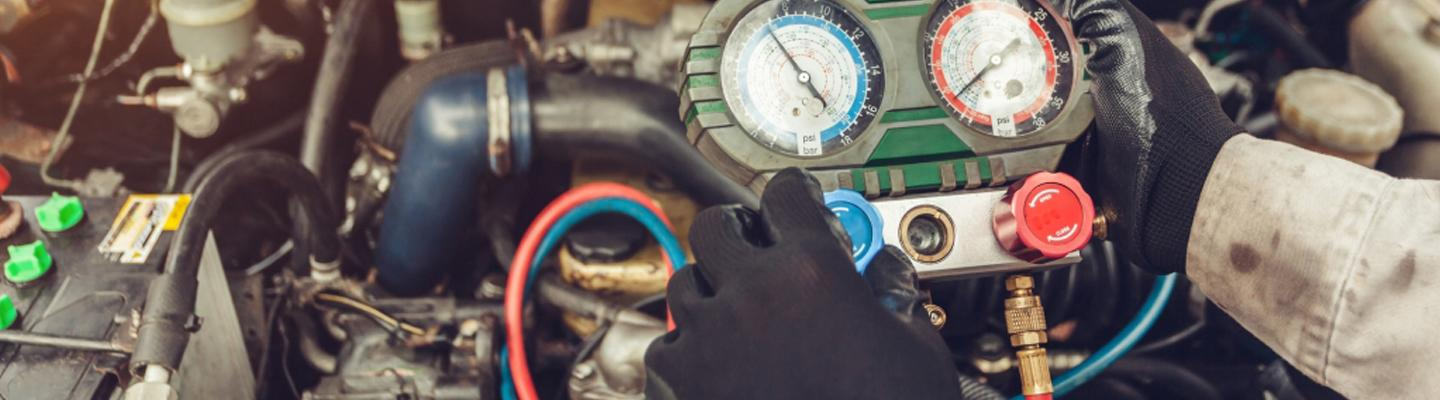Close up view of a technician measuring psi in a Volkswagen vehicle