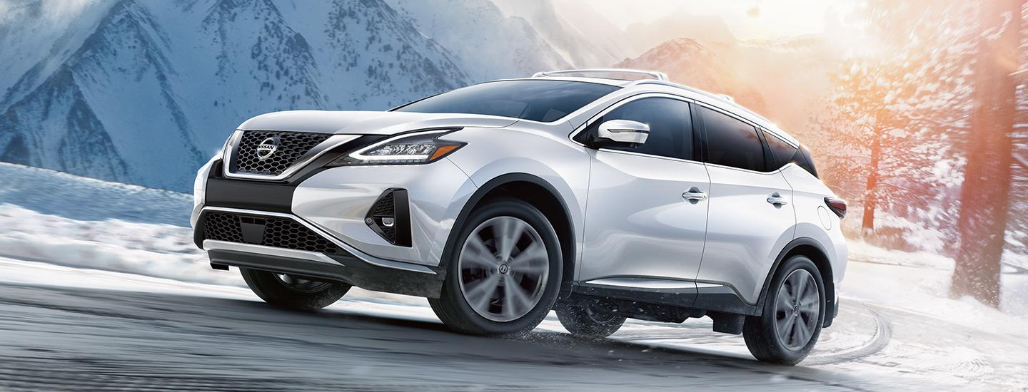 Side profile of a silver Nissan Murano driving a snowy road
