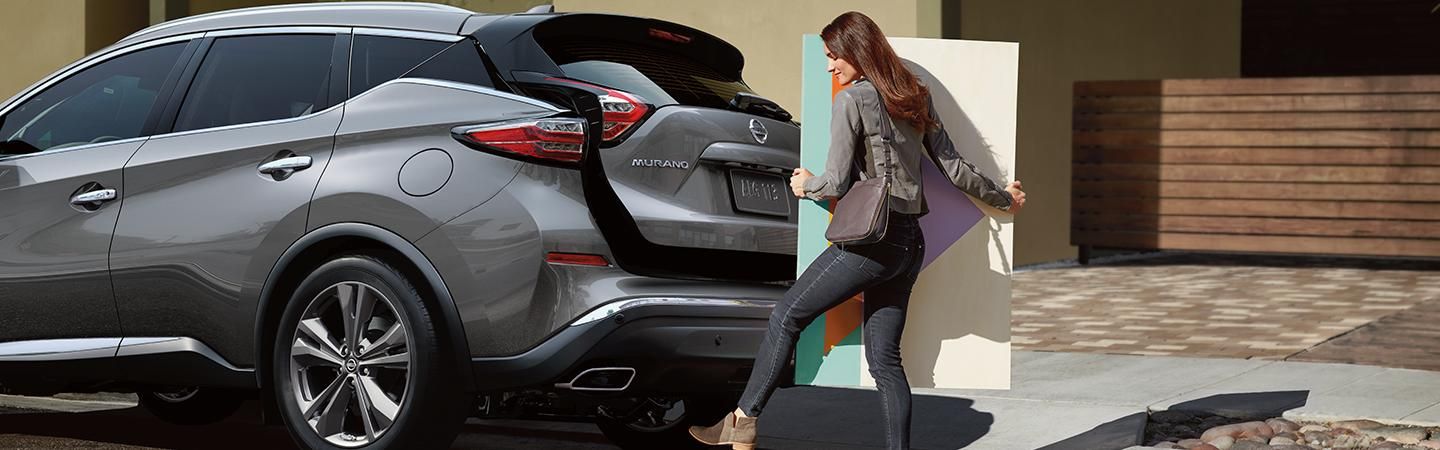 Side profile of a driver loading a painting into their Nissan Murano's trunk