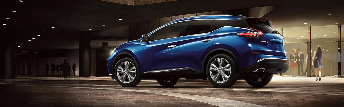 Side profile of a blue Nissan Murano parked outside of a formal event