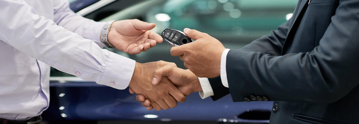 A dealership employee and customer exchanging new car keys
