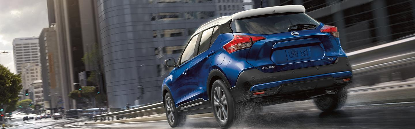 Rear view of a blue 2020 Nissan Kicks in motion