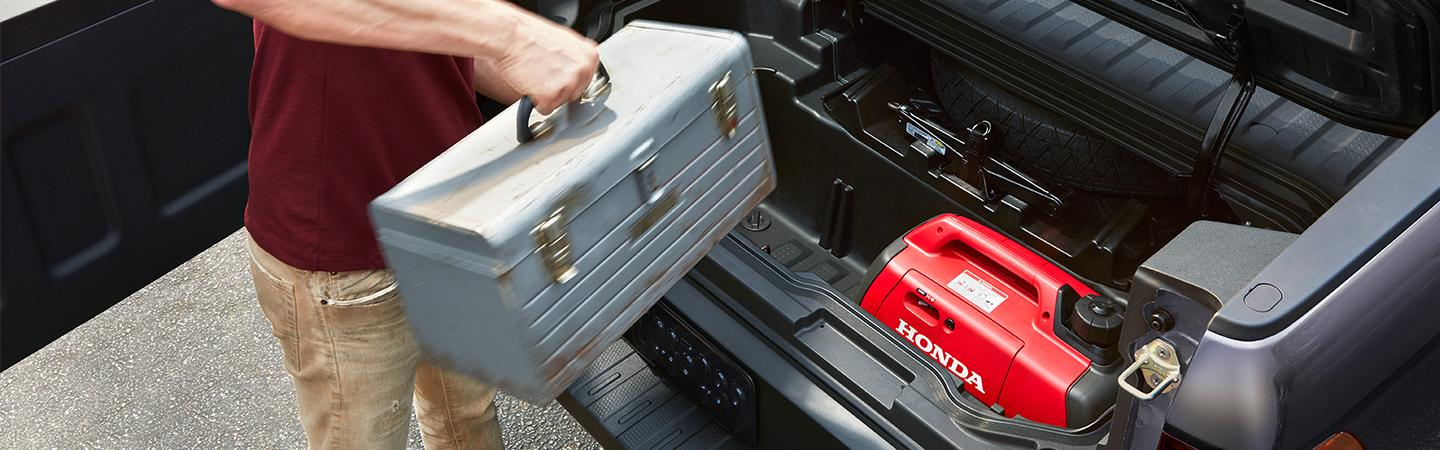 A guy loading tools into a 2021 lockable In-Bed Ridgeline trunk