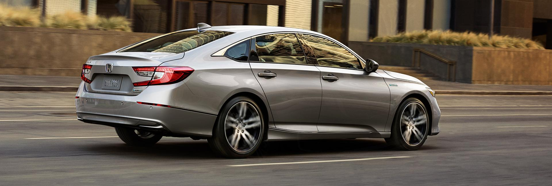 Side angled profile of a silver Honda Accord in motion