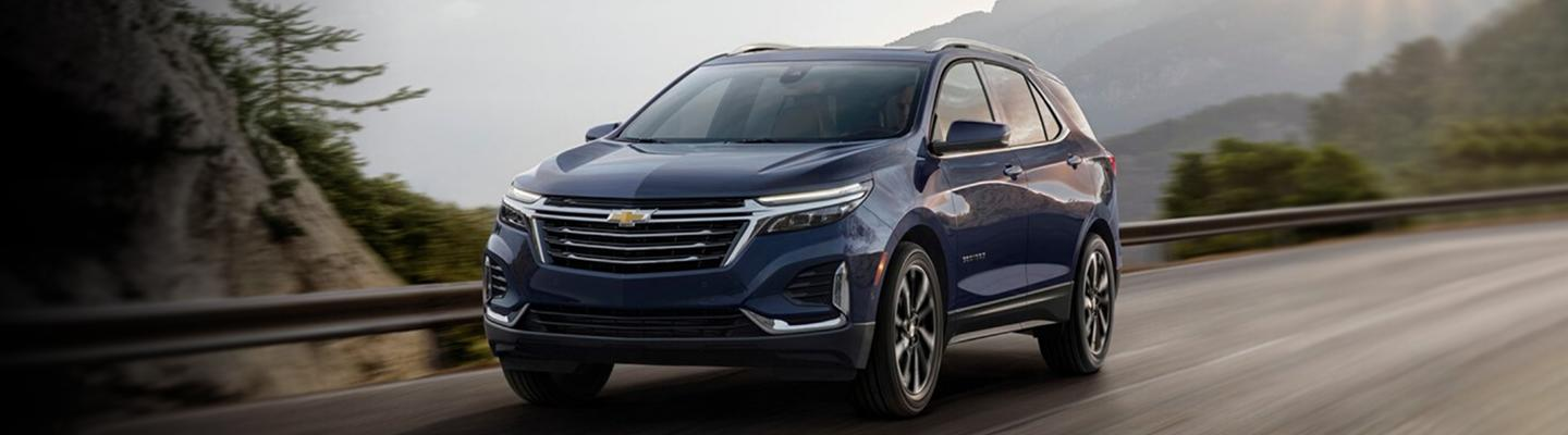 Angled profile of a blue Chevy Equinox in motion