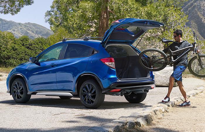 A driver loading a bike into the back of a parked blue Honda HR-V