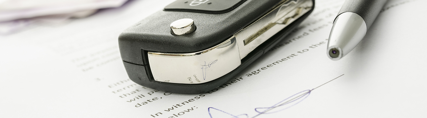 Finance paperwork with car keys and a pen on top