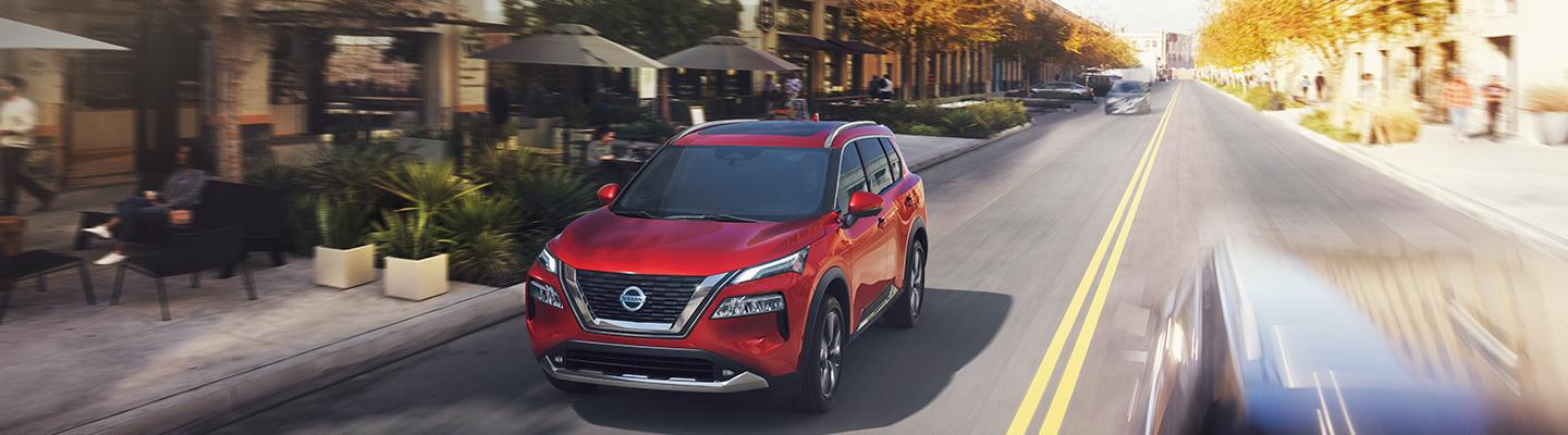Front view of a red Nissan in motion