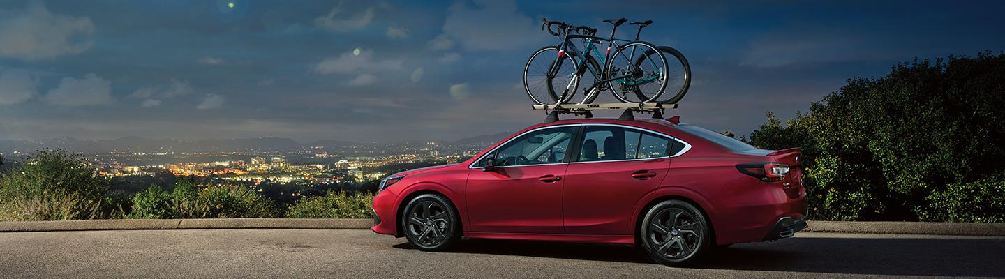 Red Subaru Legacy with bikes on roof
