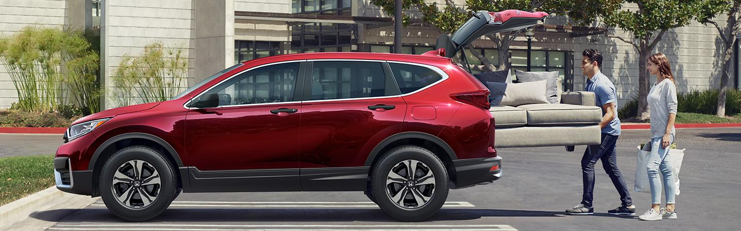 Couple loading a couch into the trunk of their red Honda CR-V