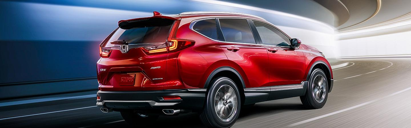 Angled rear view of a red Honda CR-V driving through a tunnel