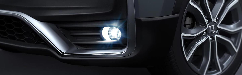 Low angled view of a black Honda CR-V's wheel and headlight