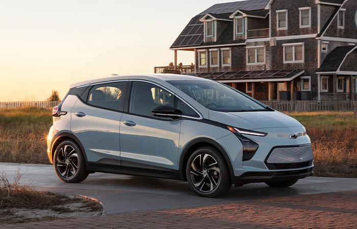 Angled profile of a Chevy Bolt EV parked in front of a house