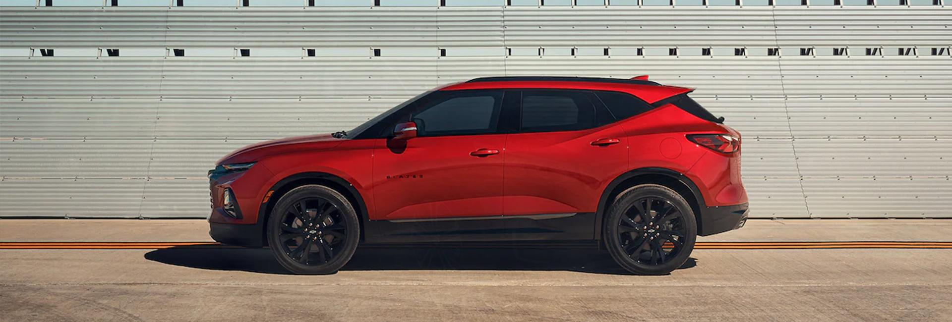 Side profile of a parked red Chevrolet Blazer