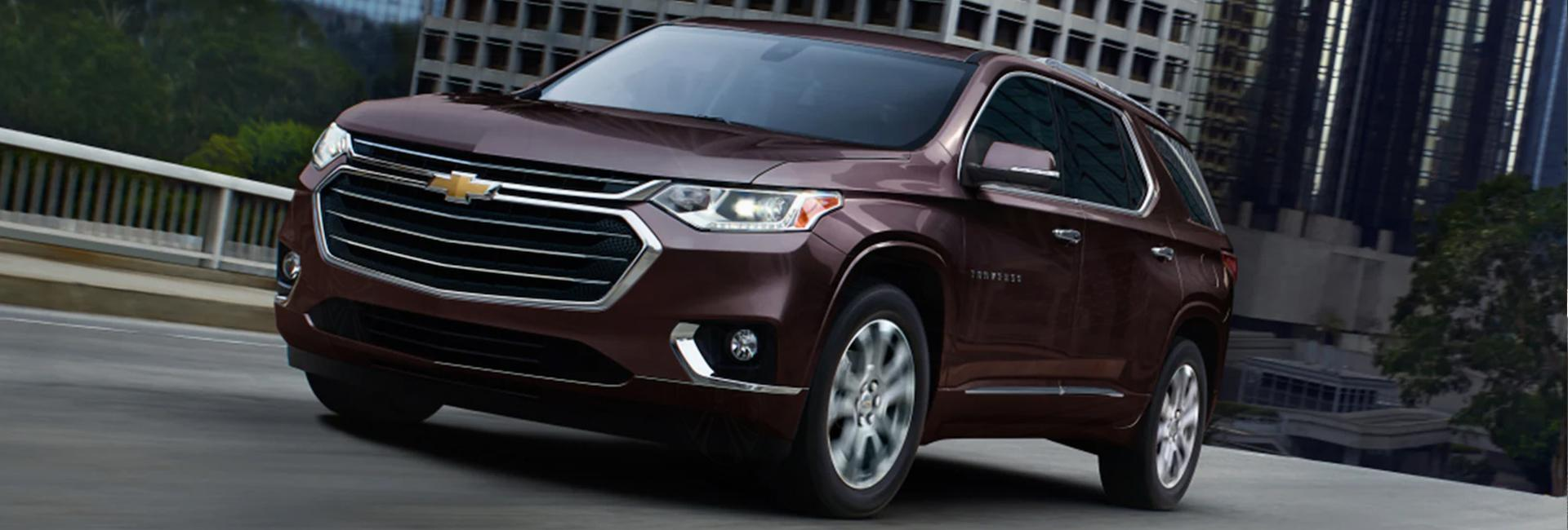 Angled profile of a burgundy Chevy Traverse in motion