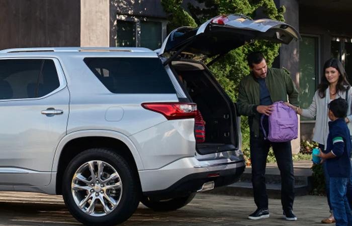 A family loading a backpack into the trunk of a Chevy Traverse