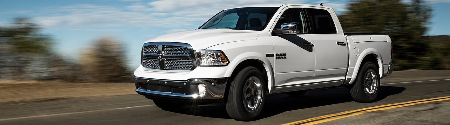 Side view of a white Certified Pre-Owned RAM in motion