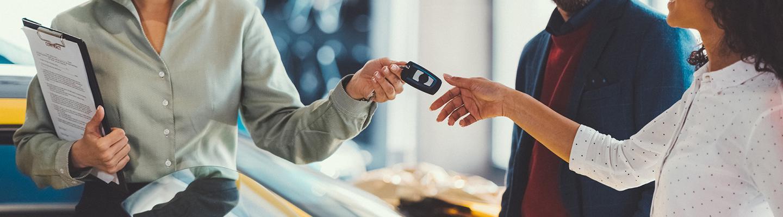 A dealership employee handing new car keys to a customer