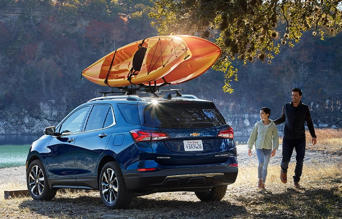 Rear view of 2022 Chevy Equinox with Kayak on roof and man standing next to vehicle